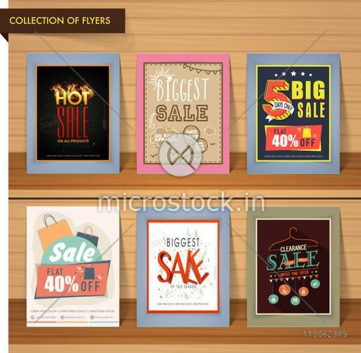 Collection of six different biggest sale flyers with discount offers on wooden background.
