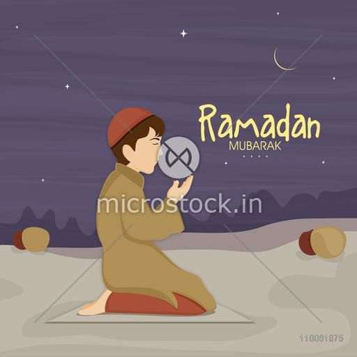 Cute little Muslim boy in traditional dress praying (reading Namaz, Islamic Prayer) in night on occasion of holy month Ramadan Kareem celebration.