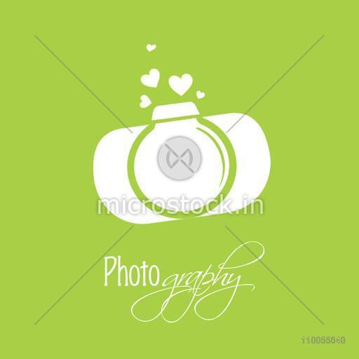 Stylish camera with hearts on green background for photography.