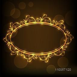 Shiny golden floral decorated frame in oval shape on brown background.