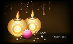 Beautiful decorative burning candles with hanging stars and Xmas ball on brown background.