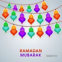 Elegant Greeting Card design decorated with colourful hanging paper lamps for Islamic Holy Month of Prayer and Fasting, Ramadan Mubarak celebration.