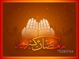 Praying human hands with Arabic Islamic Calligraphy of text Ramadan Kareem on Mosque silhouetted background.