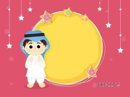 Cute Muslim Boy in Traditional Outfit with beautiful blank frame on stars decorated background for Islamic Festivals Celebration.