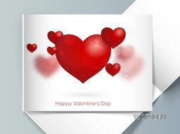 Glossy red hearts decorated elegant greeting card with envelope for Happy Valentine's Day celebration.
