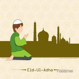 Cute little boy offering namaz infron of  Mosque with stylish text of Eid-Ul-Adha on seamless background.