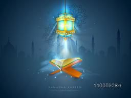 Islamic religious book Quran Shareef with rosary and illuminated Arabic lamp on Mosque silhouette background for holy month Ramadan Kareem celebration.