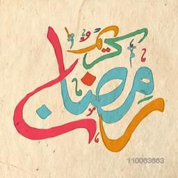 Colorful Arabic Islamic calligraphy of text Ramadan Kareem on paper texture background for Muslim community festival celebration.