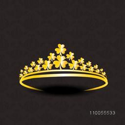 Stylish gold crown decorative by shiny golden shamrock leaves on seamless dark brown background.