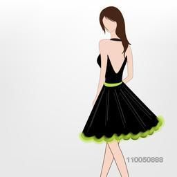 Young modern girl wearing a stylish black beckless dress with green print.