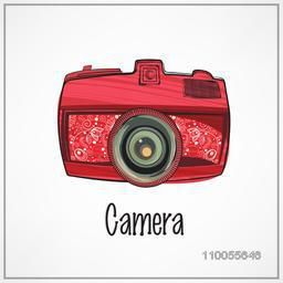 Stylish photographic camera in red color with floral design decoration on grey background.