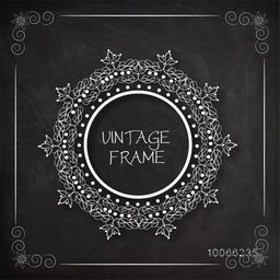 Floral design decorated beautiful rounded vintage frame created by white chalk on blackboard background.