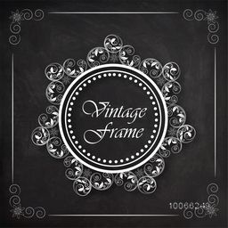 Stylish vintage frame decorated by floral design on blackboard background.