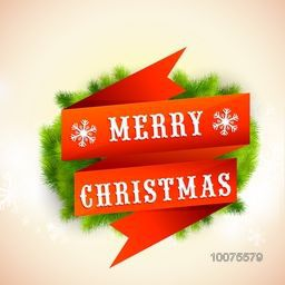 Glossy fir tree branches decorated greeting card with orange ribbon for Merry Christmas celebration.