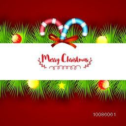 Elegant Greeting Card design decorated with shiny fir branches, candy canes and xmas balls on red background.