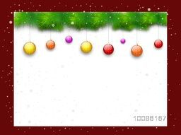 Blank board decorated with colorful hanging balls and fir tree branches for Merry Christmas celebration concept.