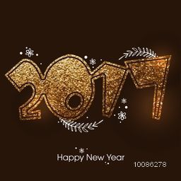 Golden glittering text 2017 on brown background for Happy New Year celebration.