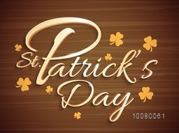 3D glossy typography of St. Patrick's Day on Shamrock leaves decorated, Wooden background.