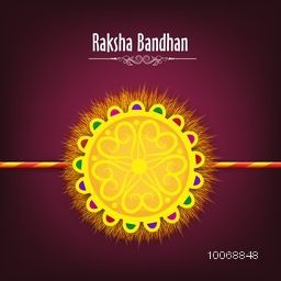 Beautiful yellow rakhi on purple background for Indian festival of brother and sister love, Happy Raksha Bandhan celebration.