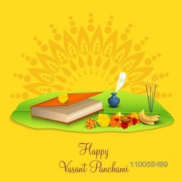 Hindu Community festival, Vasant Panchami celebration with religious book, ink pot and religious offerings on floral decorated yellow background.
