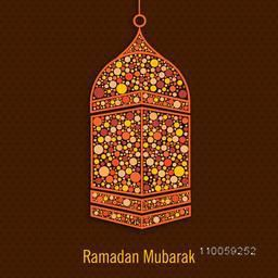 Beautiful decorated lamp hanging on brown background for holy month of Muslim community Ramadan Kareem celebration.