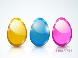 Glossy three colorful eggs for Happy Easter celebration on shiny sky blue background.