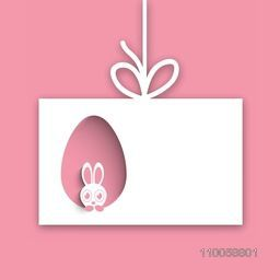 Cute bunny looking out from paper cutout egg shape for Happy Easter celebration.