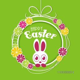 Happy Easter celebration with cute bunny looking out from colorful flowers decorated hanging ball on green background.